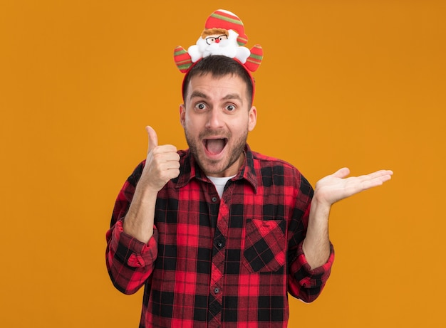 Geïmponeerde jonge blanke man met de hoofdband van de kerstman kijken naar camera met duim omhoog en lege hand geïsoleerd op een oranje achtergrond