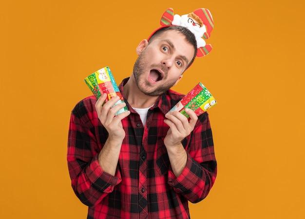 Geïmponeerde jonge blanke man met hoofdband van de kerstman met plastic kerstbekers geïsoleerd op oranje muur met kopie ruimte