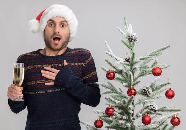 Geïmponeerde jonge blanke man met kerstmuts staande in de buurt van de kerstboom met glas champagne kijken camera hand houden op de borst geïsoleerd op een witte achtergrond
