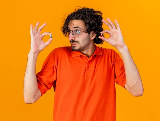 Geïmponeerde jonge blanke zieke man met bril houden en kijken naar medische capsules geïsoleerd op een oranje achtergrond