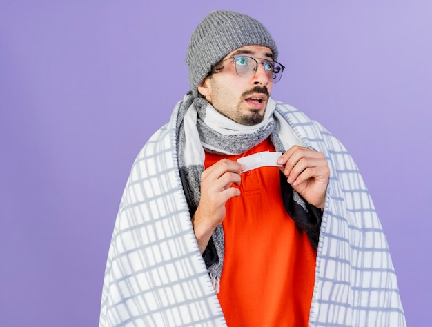 Geïmponeerde jonge blanke zieke man met bril, muts en sjaal gewikkeld in plaid kijken kant houden medische gips geïsoleerd op paarse achtergrond met kopie ruimte
