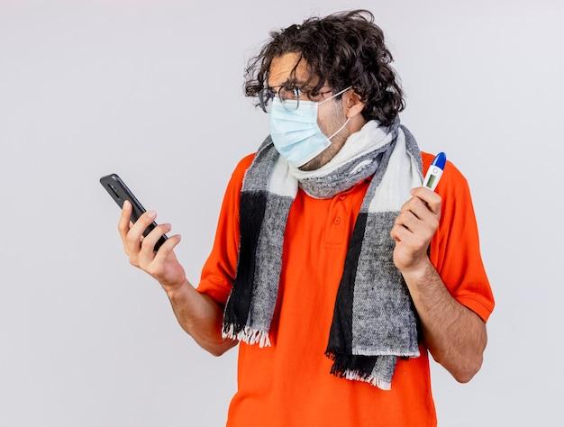 Geïmponeerde jonge blanke zieke man met bril, sjaal en masker met thermometer en mobiele telefoon kijken naar telefoon geïsoleerd op een witte muur