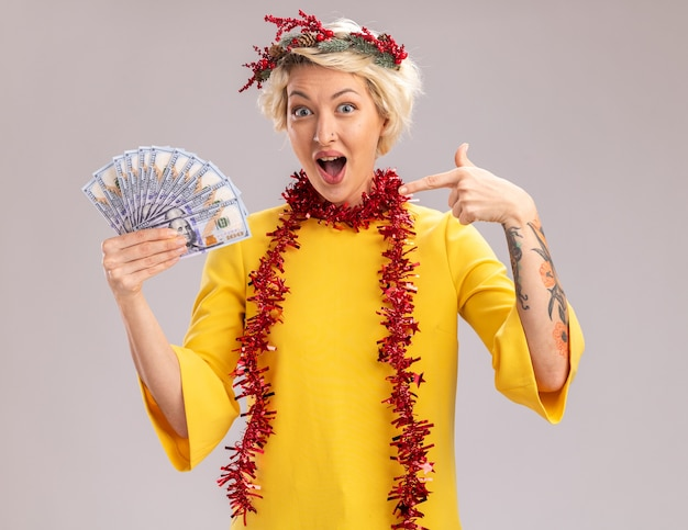 Geïmponeerde jonge blonde vrouw die de kroon van kerstmis en klatergoudslinger om hals draagt ?? die en op geld houdt die camera bekijkt die op witte achtergrond wordt geïsoleerd