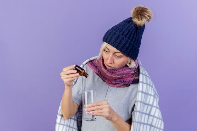 Geïmponeerde jonge blonde zieke slavische vrouw die de wintermuts en sjaal draagt