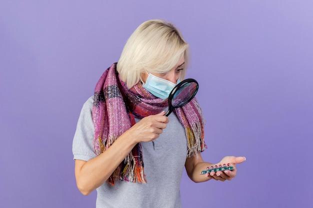 Geïmponeerde jonge blonde zieke slavische vrouw die medische masker en sjaal draagt