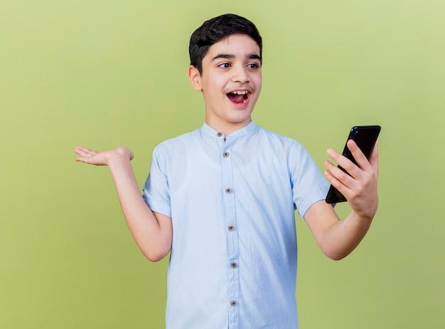 Geïmponeerde jonge jongen die en mobiele telefoon houdt bekijkt die lege die hand toont die op olijfgroene muur wordt geïsoleerd