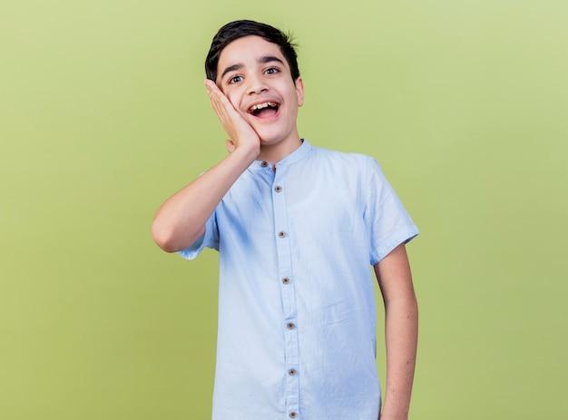 Geïmponeerde jonge jongen die hand op gezicht houdt die voorzijde bekijkt die op olijfgroene muur wordt geïsoleerd
