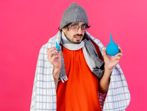 Geïmponeerde jonge kaukasische zieke man met bril, muts en sjaal verpakt in plaid bedrijf klysma's kijken camera geïsoleerd op crimson achtergrond met kopie ruimte