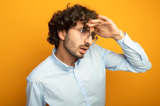 Geïmponeerde jonge knappe man die een bril draagt die hand op voorhoofd houdt die kant in afstand bekijkt die op oranje muur wordt geïsoleerd