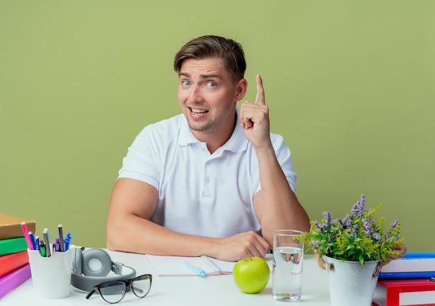 Geïmponeerde jonge knappe mannelijke student zittend aan een bureau met schoolhulpmiddelen wijst naar boven op olijfgroen