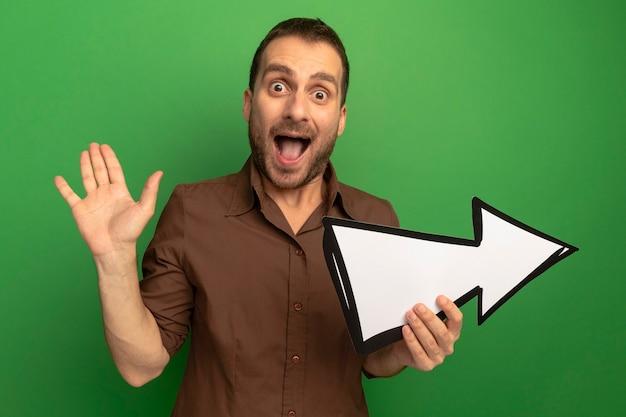 Geïmponeerde jonge man die naar de voorkant kijkt die pijlteken wijst die naar kant wijst die lege hand toont die op groene muur wordt geïsoleerd