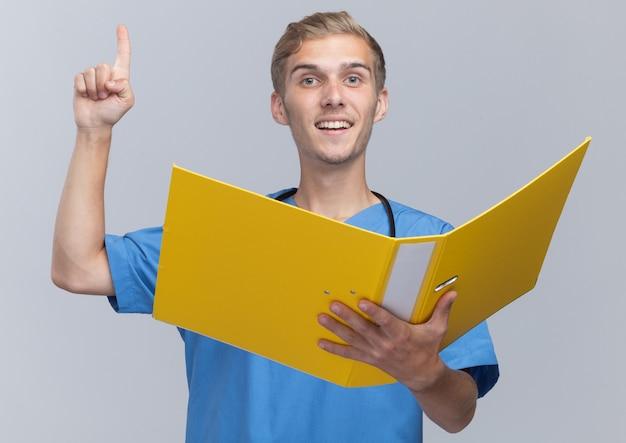 Geïmponeerde jonge mannelijke arts die artsenuniform met de map van de stethoscoopholding draagt wijst omhoog geïsoleerd op witte muur