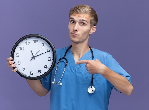 Geïmponeerde jonge mannelijke arts die artsenuniform met stethoscoopholding draagt en wijst op muurklok die op blauwe muur wordt geïsoleerd