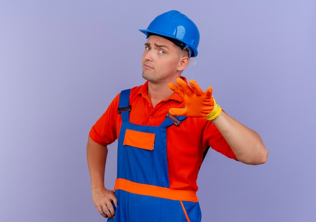 Geïmponeerde jonge mannelijke bouwer die eenvormig en veiligheidshelm in handschoenen draagt die hand standhouden