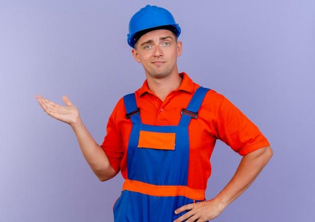Geïmponeerde jonge mannelijke bouwer die uniform en veiligheidshelmpunten met hand aan kant draagt