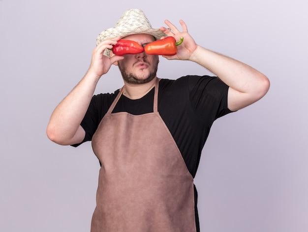 Geïmponeerde jonge mannelijke tuinman die het tuinieren hoed draagt die blikgebaar met paprika toont die op witte muur wordt geïsoleerd