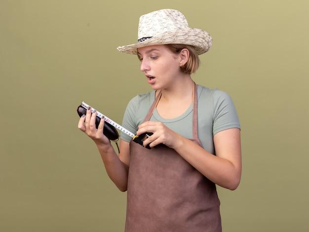 Geïmponeerde jonge slavische vrouwelijke tuinman die het tuinieren hoed draagt die aubergine met meetlint op olijfgroen meet