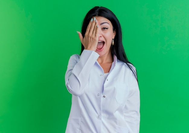 Geïmponeerde jonge vrouwelijke arts die medisch kleed draagt dat de helft van gezicht bedekt met hand die op groene muur met exemplaarruimte wordt geïsoleerd