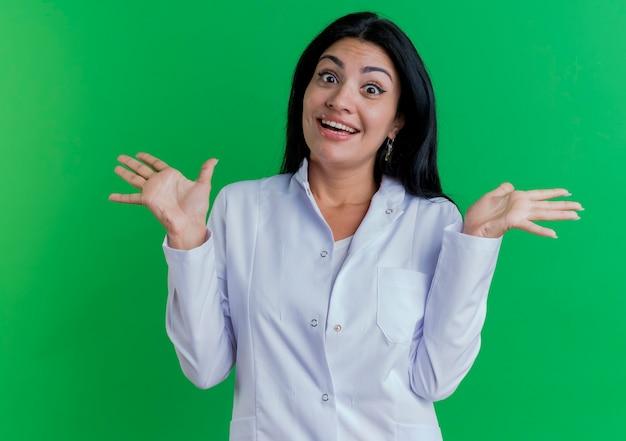 Geïmponeerde jonge vrouwelijke arts die medische mantel draagt en lege handen toont