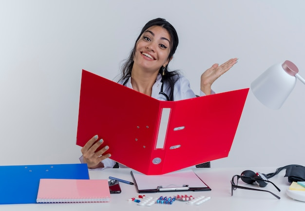 Geïmponeerde jonge vrouwelijke arts die medische mantel en stethoscoop draagt die aan bureau met medische hulpmiddelen zit die holdingsomslag kijkt die lege geïsoleerde hand toont