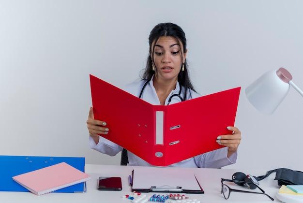 Geïmponeerde jonge vrouwelijke arts die medische mantel en stethoscoop draagt die aan bureau met medische hulpmiddelen zitten die en geïsoleerde map bekijken