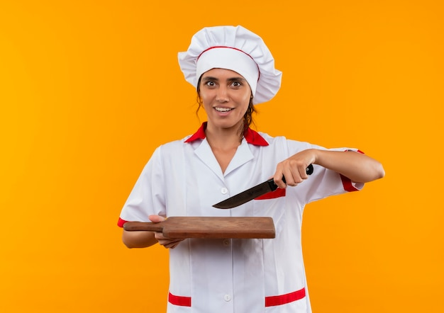 Geïmponeerde jonge vrouwelijke kok die het mes van de chef-kok het uniforme vasthouden en snijplank op geïsoleerde gele muur met exemplaarruimte draagt