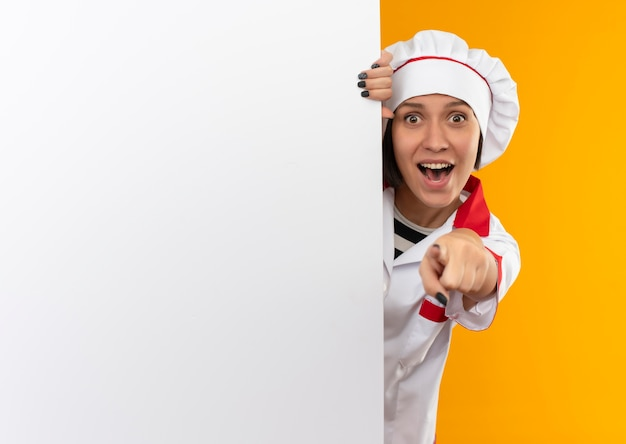 Geïmponeerde jonge vrouwelijke kok in eenvormige chef-kok die zich achter witte muur bevindt en geïsoleerd op oranje met exemplaarruimte richt