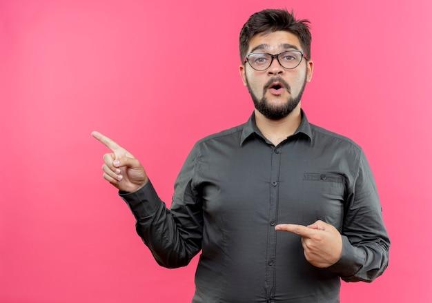 Geïmponeerde jonge zakenman die glazen wijst aan kant die op roze muur met exemplaarruimte wordt geïsoleerd