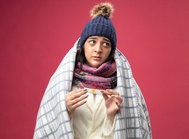 Geïmponeerde jonge zieke vrouw die de muts en de sjaal van de gewaadwinter draagt die in plaid wordt verpakt die medische pleister houdt die kant bekijkt die op roze muur wordt geïsoleerd