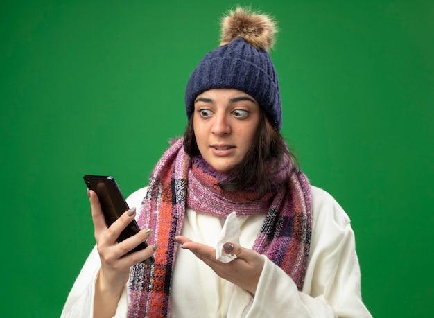 Geïmponeerde jonge zieke vrouw die de muts en de sjaal van de robe-winter draagt ?? die en naar mobiele telefoon kijkt kijkt ernaar met servet in de hand geïsoleerd op groene muur