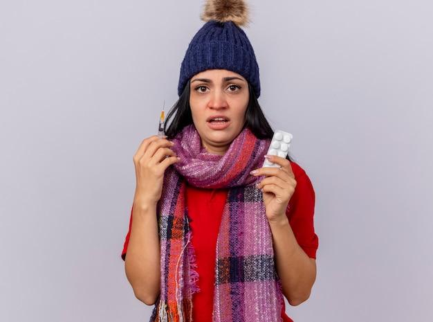 Geïmponeerde jonge zieke vrouw die de winterhoed en sjaal draagt die spuit en pak tabletten bekijkt die voorzijde op witte muur wordt geïsoleerd
