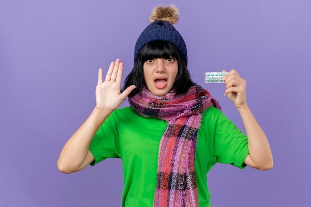 Geïmponeerde jonge zieke vrouw die de wintermuts en sjaal draagt die aan de voorkant kijken met pak capsules die lege hand tonen die op paarse muur wordt geïsoleerd