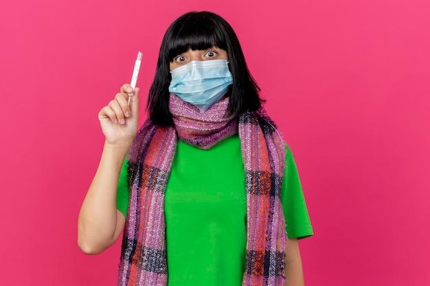 Geïmponeerde jonge zieke vrouw die masker en sjaal draagt die thermometer houdt die voorzijde bekijkt die op roze muur met exemplaarruimte wordt geïsoleerd