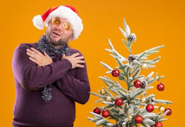 Geïmponeerde man van middelbare leeftijd met kerstmuts en klatergoud slinger om nek met bril staande in de buurt van versierde kerstboom opzoeken met handen gekruist op schouders op oranje muur