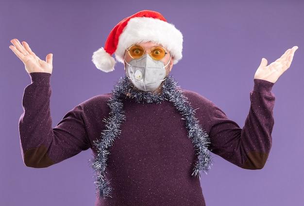 Geïmponeerde man van middelbare leeftijd met kerstmuts en klatergoud slinger rond de nek met bril en beschermend masker camera kijken