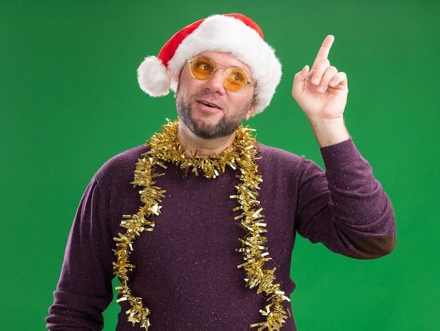 Geïmponeerde man van middelbare leeftijd met kerstmuts en klatergoud slinger rond de nek met bril kijken naar kant omhoog geïsoleerd op groene achtergrond