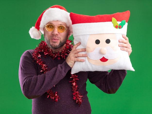 Geïmponeerde man van middelbare leeftijd met kerstmuts en klatergoudslinger om nek met bril die kerstman kussen houdt dat op groene muur wordt geïsoleerd