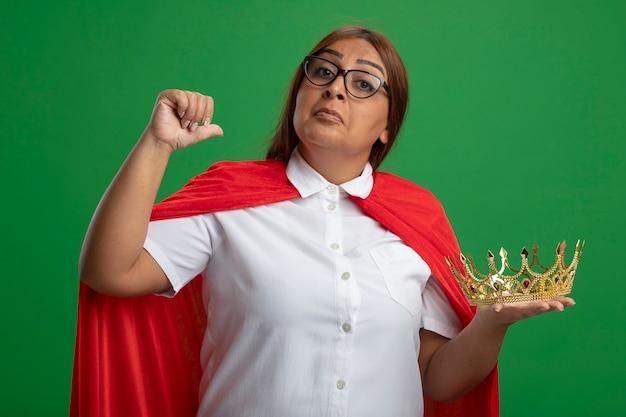 Geïmponeerde superheldvrouw van middelbare leeftijd die glazen draagt die kroonpunten op zichzelf houden die op groene achtergrond worden geïsoleerd