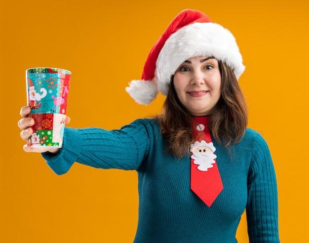 Geïmponeerde volwassen blanke vrouw met kerstmuts en santa stropdas met papieren beker geïsoleerd op een oranje achtergrond met kopie ruimte