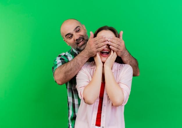 Geïmponeerde volwassen paarman die zich achter vrouw bevindt die de ogen van de vrouw behandelt met handen vrouw die handen op gezicht zet