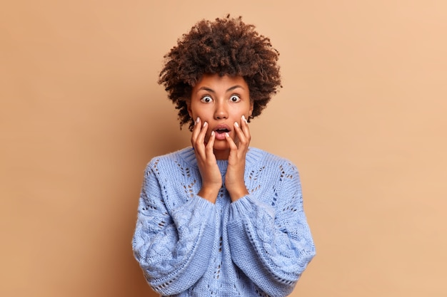 Geïmponeerde vrouw met krullend haar grijpt gezicht als ze iets schokkends ziet en adembenemende oogjes aan de voorkant hoort vreselijk nieuws, gekleed in casual trui-poses tegen de bruine muur