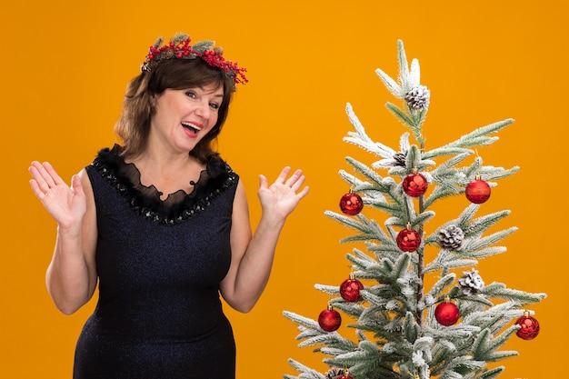 Geïmponeerde vrouw van middelbare leeftijd die kerstmis hoofdkroon en klatergoudslinger om hals draagt die dichtbij verfraaide kerstboom staat die camera bekijkt
