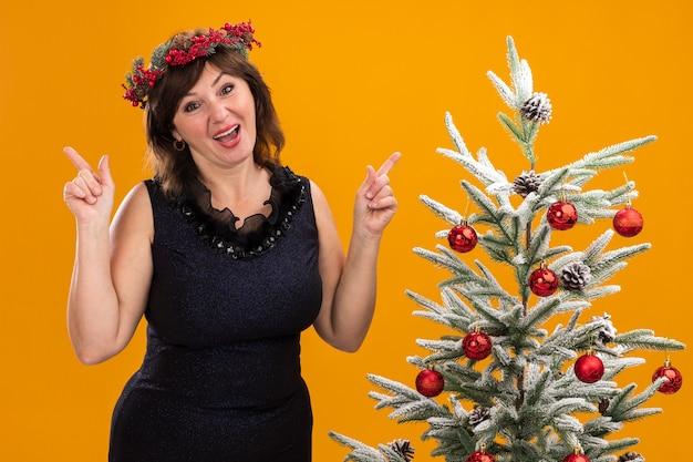 Geïmponeerde vrouw van middelbare leeftijd die kerstmis hoofdkroon en klatergoudslinger om hals draagt die zich dichtbij verfraaide kerstboom bevindt
