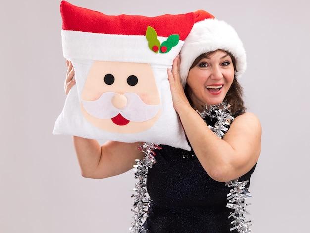 Geïmponeerde vrouw van middelbare leeftijd dragen kerstmuts en klatergoud slinger om nek met kerstman kussen hoofd aanraken met het kijken naar camera geïsoleerd op witte achtergrond