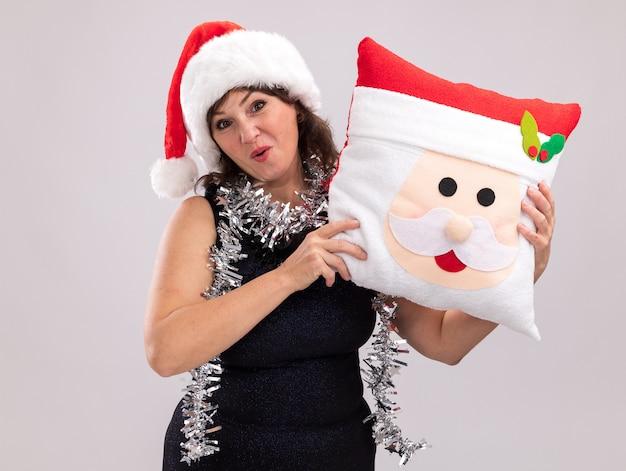 Geïmponeerde vrouw van middelbare leeftijd met kerstmuts en klatergoud slinger rond de nek met het kussen van de kerstman kijken naar camera geïsoleerd op een witte achtergrond