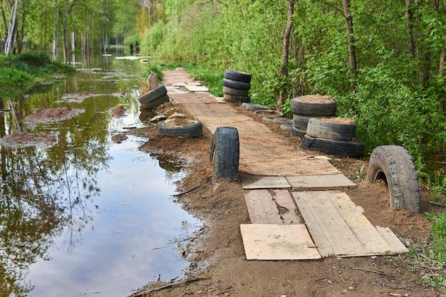 Geïmproviseerde bestrating op de dijk werd gemaakt op het platteland tijdens een overstroming van de lenterivier