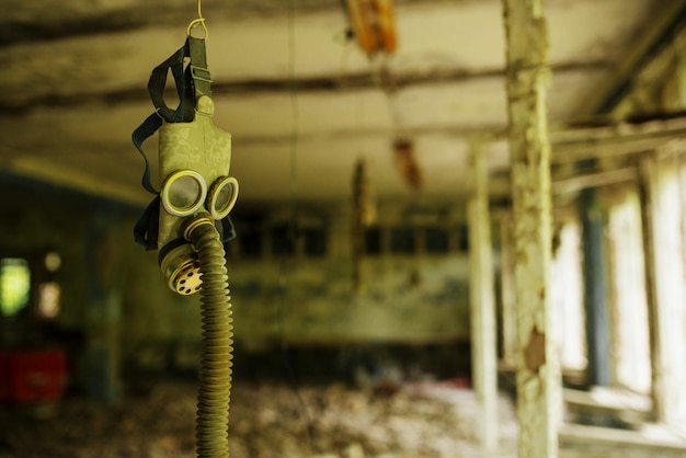 Geïnfecteerd stralingsgasmasker in een verlaten middelbare school in de vervreemdende zone van de kerncentrale van tsjernobyl