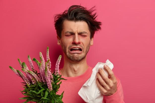 Geïnfecteerde man snuit neus in weefsel, heeft allergiesymptomen in de lente, kan niet goed ademen, niest constant, houdt de plant vast, huilt en voelt zich moe van de behandeling. immunotherapie concept
