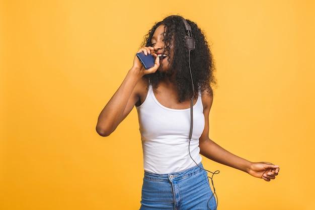 Geïnspireerd afro-amerikaanse dame muziek luisteren, dansen met gesloten ogen