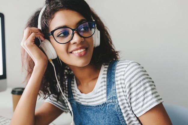 Geïnspireerd brunette meisje met een gebruinde huid lachen tijdens het luisteren naar muziek op kantoor